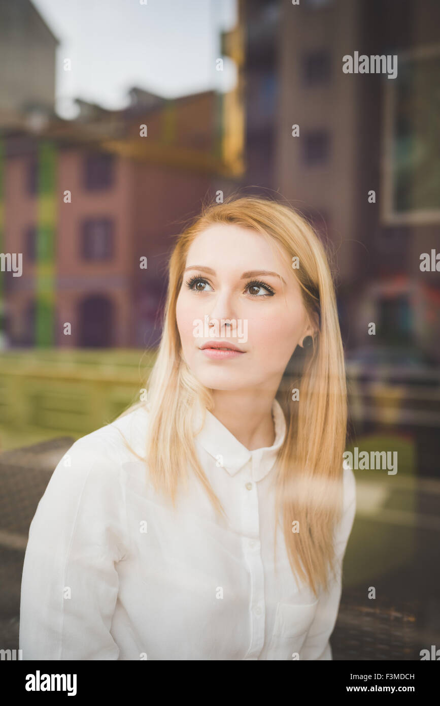 Half length of young beautiful blonde straight hair woman in the city sitting at the restaurant, view behind a shop - Stock Image