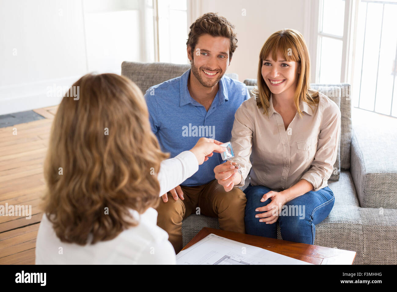 Young owners couple receive the keys of their new house - Stock Image
