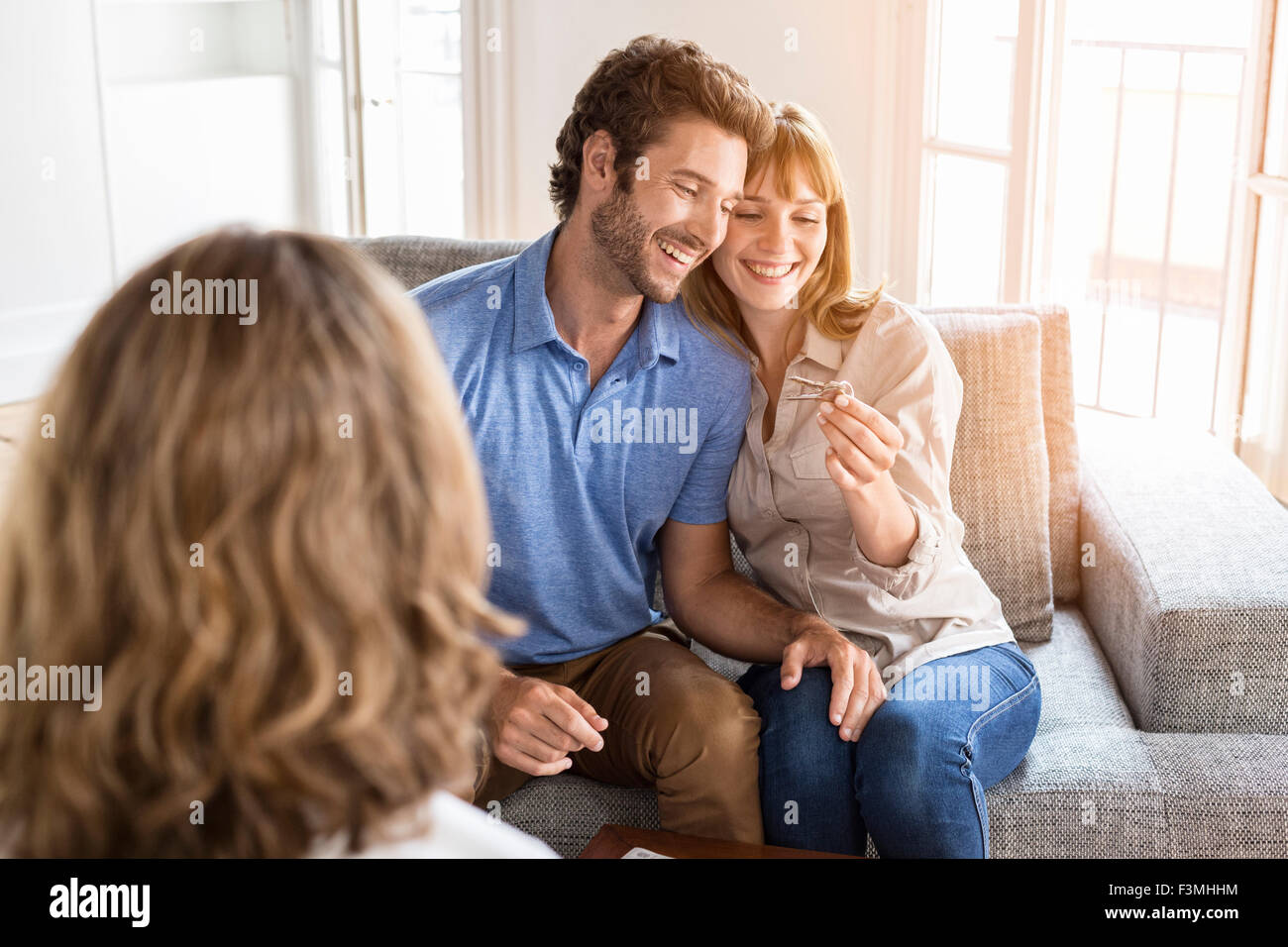 Saleswoman giving apartment keys to new owners. Happiness, enjoyment - Stock Image
