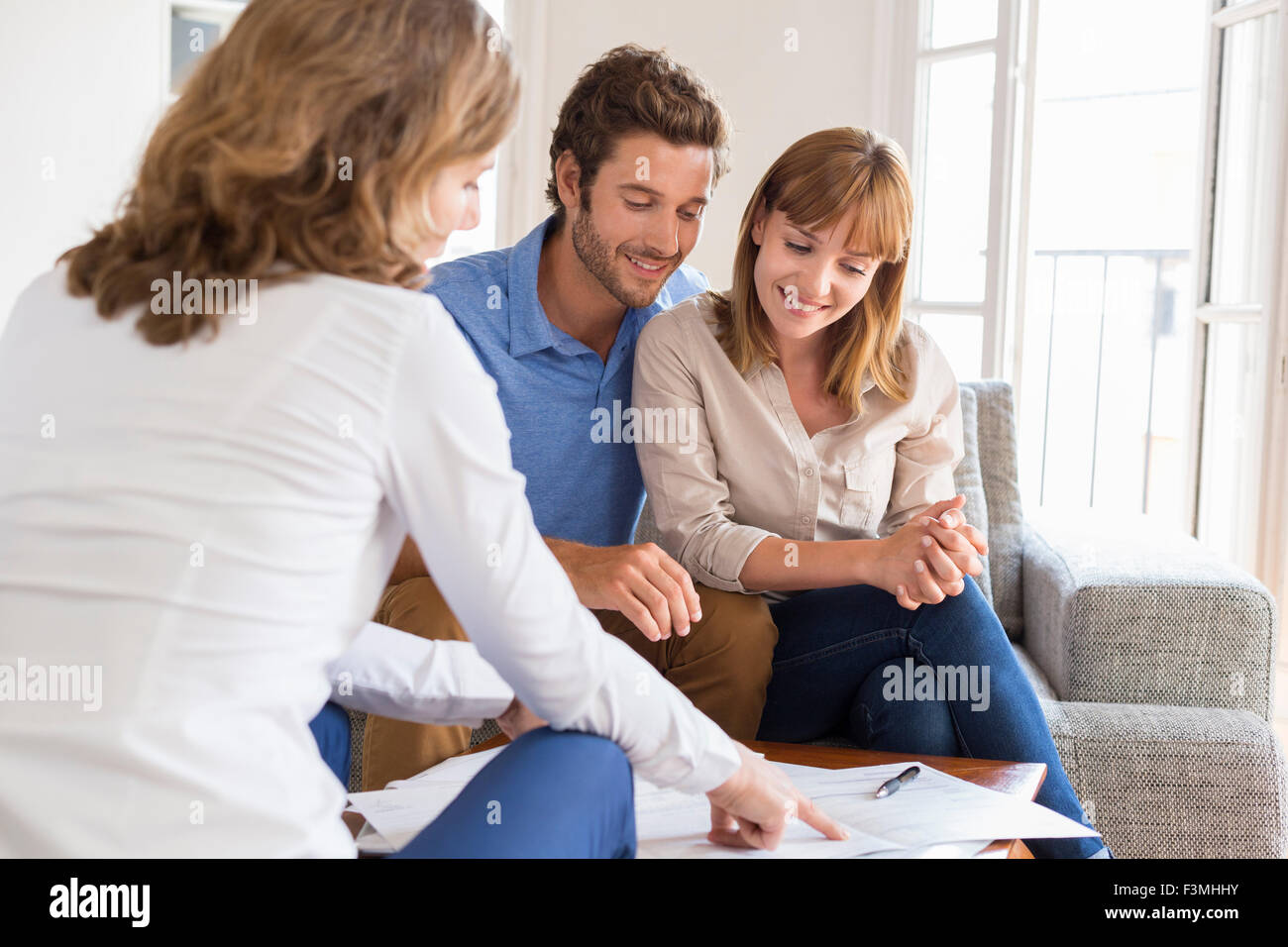 Real estate agent presenting a contract for house investment to future owners couple - Stock Image