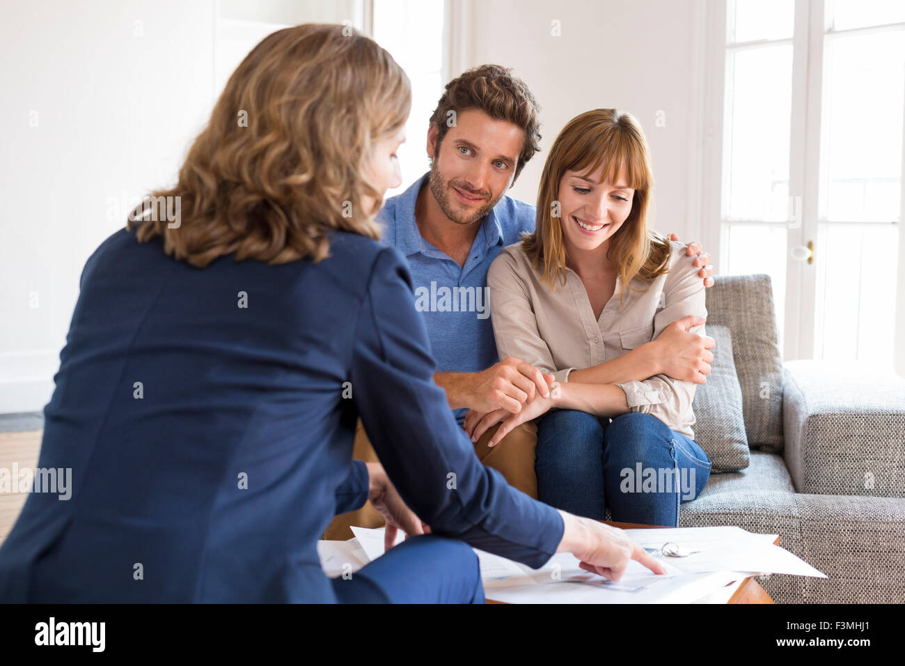 Realtor agent presenting a contract for apartment investment to future owners couple - Stock Image