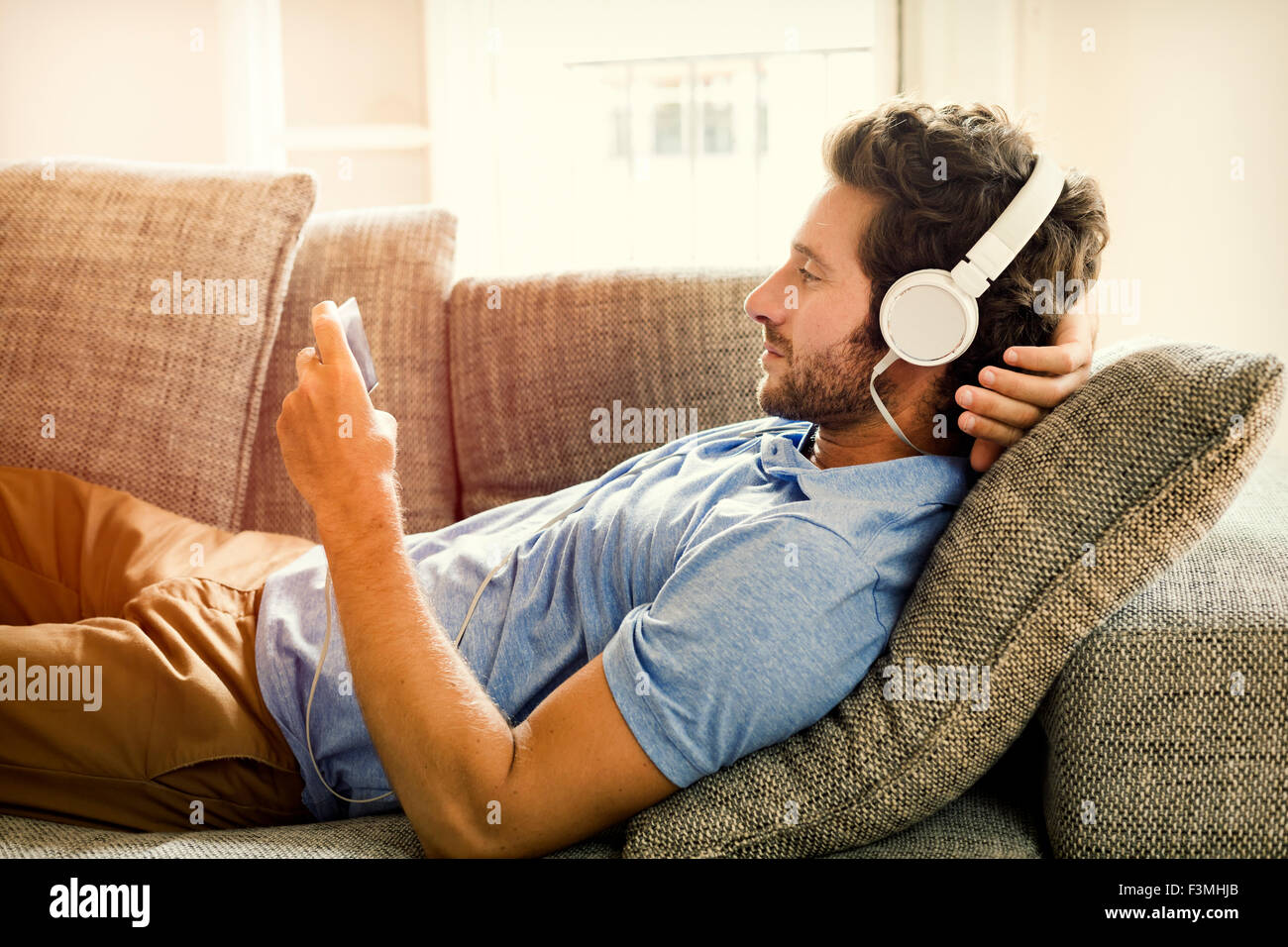 Man on couch watches a movie on mobile phone. Lens flare - Stock Image