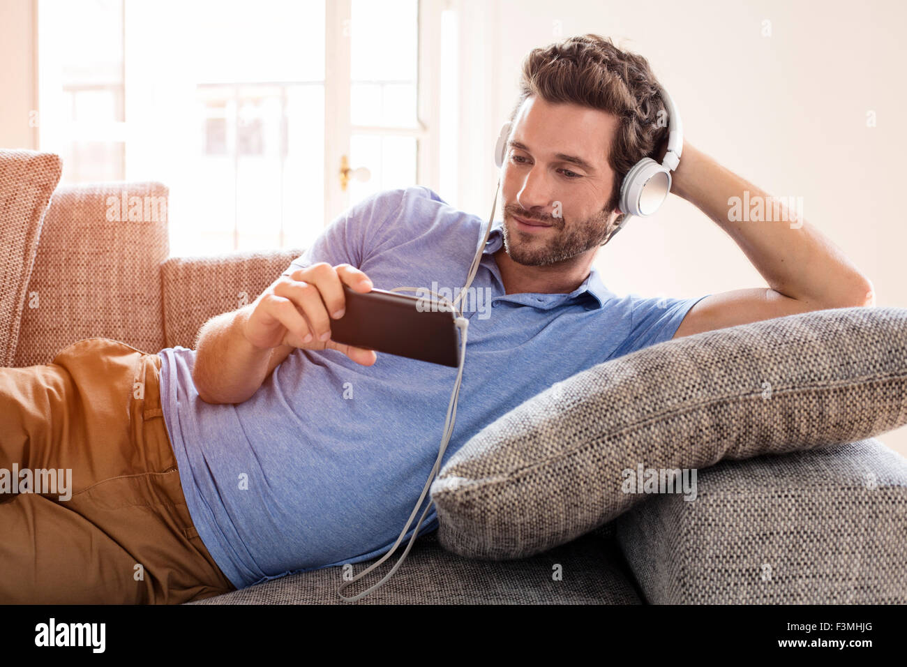 Man at home watches a movie on cell phone - Stock Image