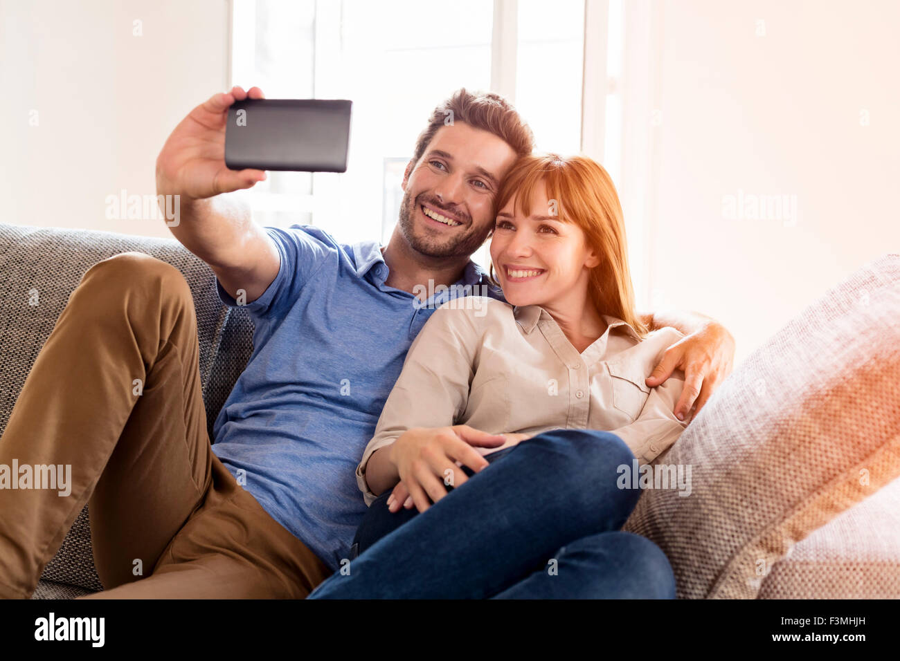 Happy couple in love taking a selfportrait with a cell phone. Home sofa. Lens flare - Stock Image