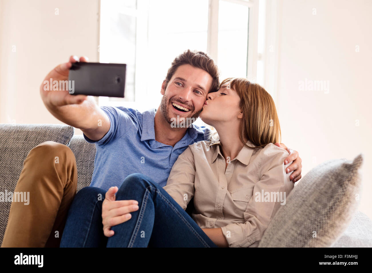 Couple in love taking a selfie with a mobile phone. it makes him a kiss Stock Photo