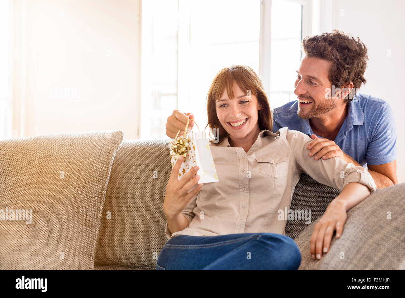 Man offering a gift to his wife for birthday. Gift, sofa, home, girlfriend, couple - Stock Image