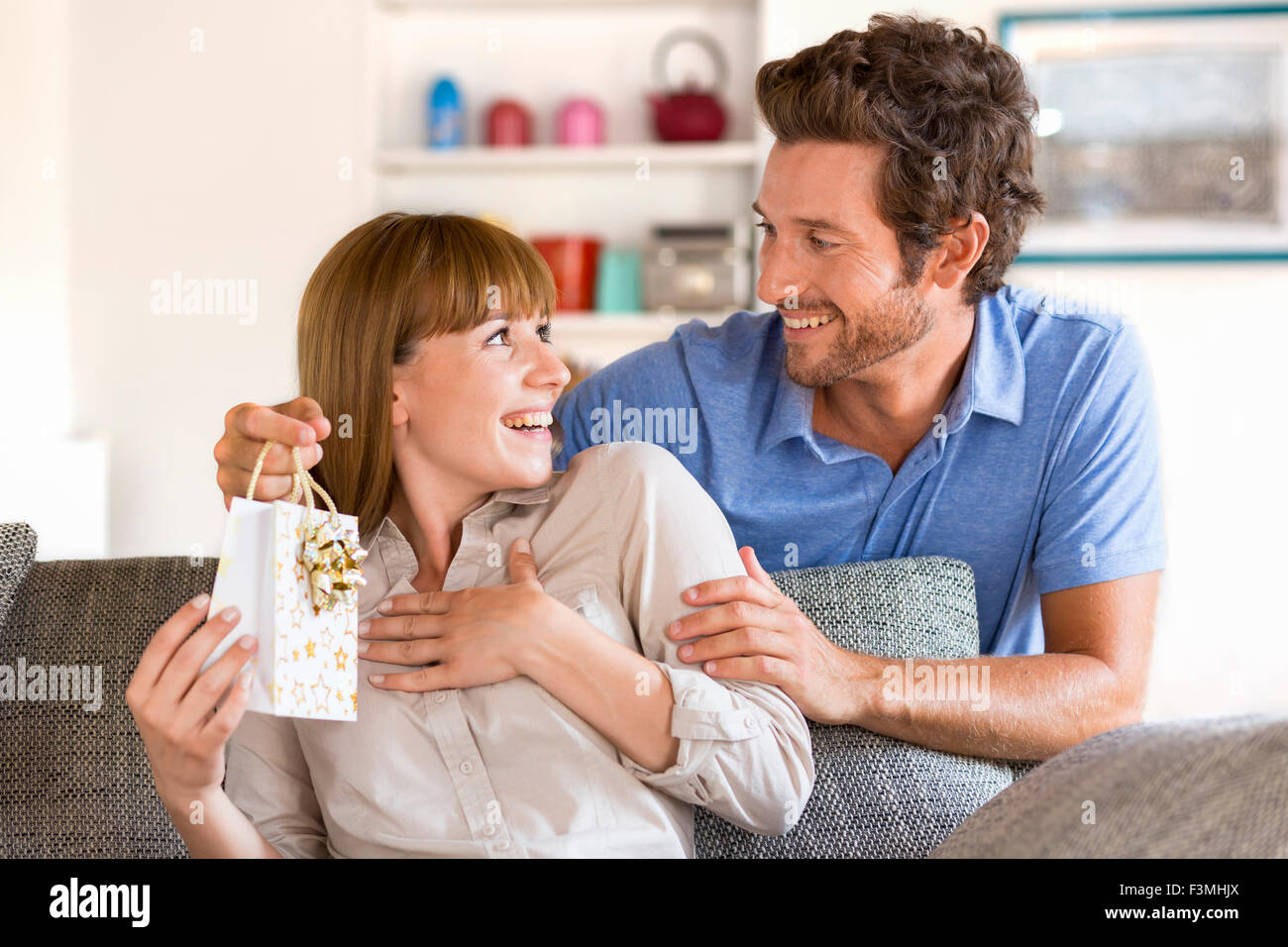 Man offering a gift to his wife for Valentine's Day. Gift, sofa, home, girlfriend, couple - Stock Image