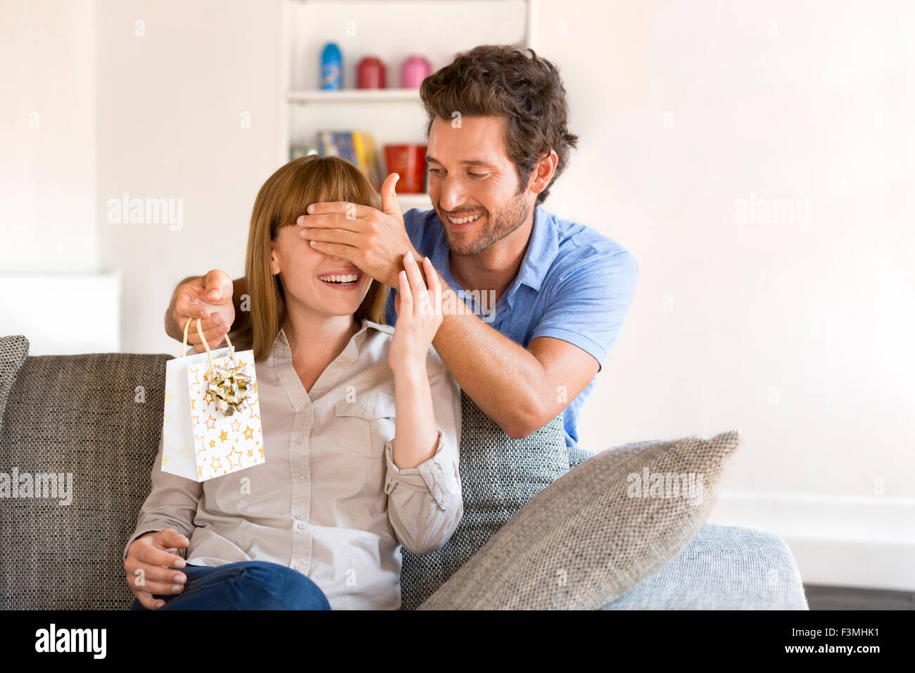 This gift for the woman of my life. Home, surprise, couch, present, couple, valentine - Stock Image