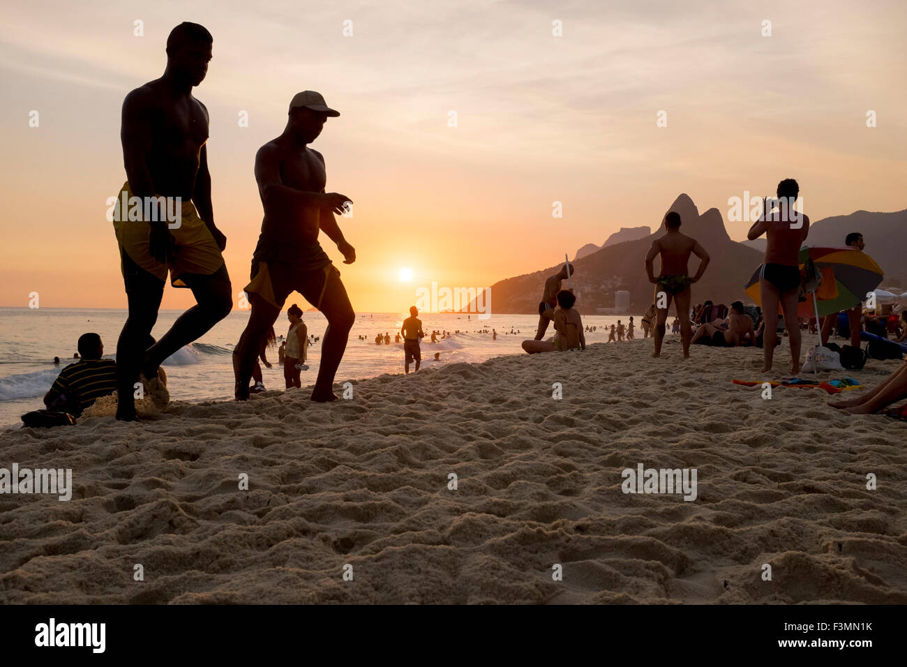 RIO DE JANEIRO, BRAZIL - FEBRUARY 21, 2014: Silhouettes of people walk along Ipanema Beach at sunset. - Stock Image