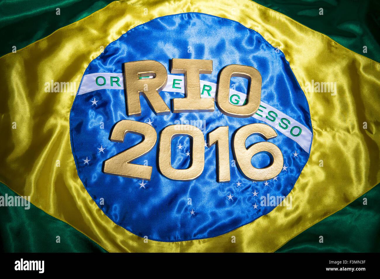 RIO DE JANEIRO, BRAZIL - FEBRUARY 3, 2015: Rio 2016 message in gold letters sits across shiny Brazilian flag. - Stock Image