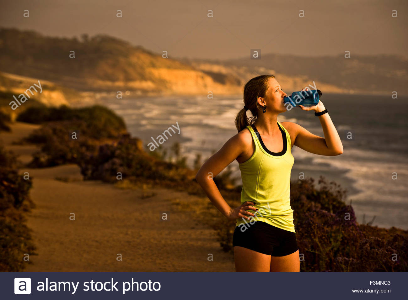 A female runner drinks from a water bottle. - Stock Image