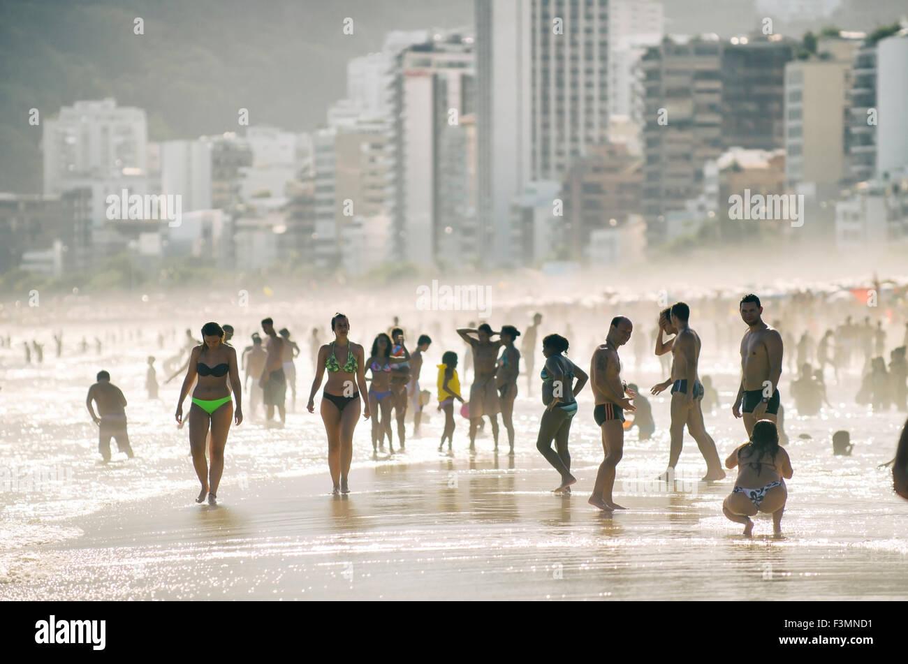 RIO DE JANEIRO, FEBRUARY 23, 2014: Silhouettes of beachgoers stand on the shore of Ipanema Beach against the city - Stock Image