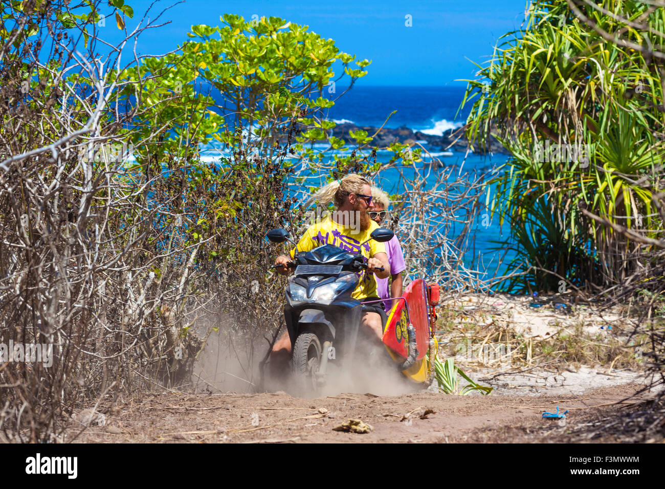 Two surfers travelling by bike.Sumbawa island.Indonesia. - Stock Image