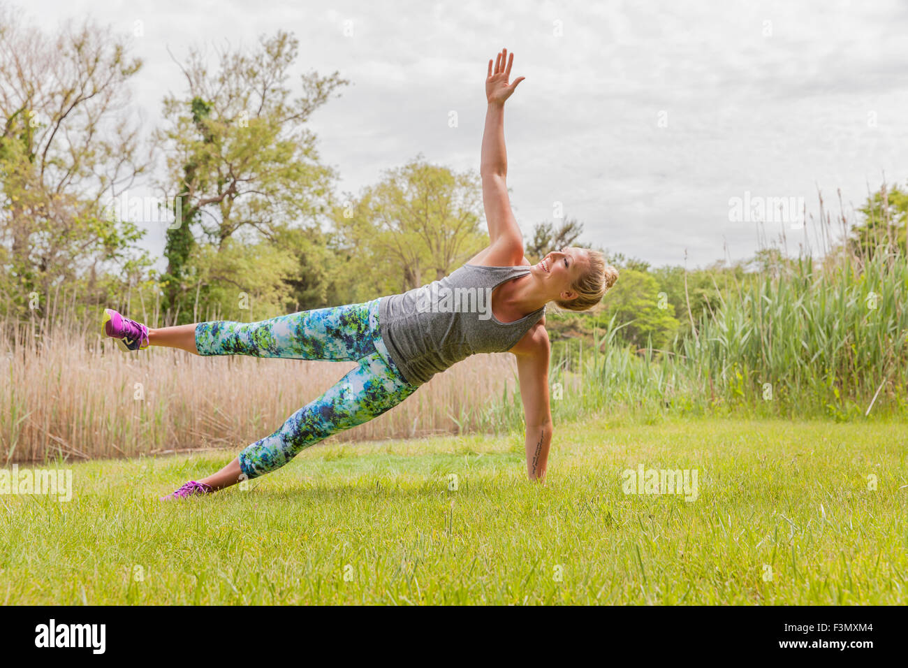 Woman in side plank pose with raised leg - Stock Image