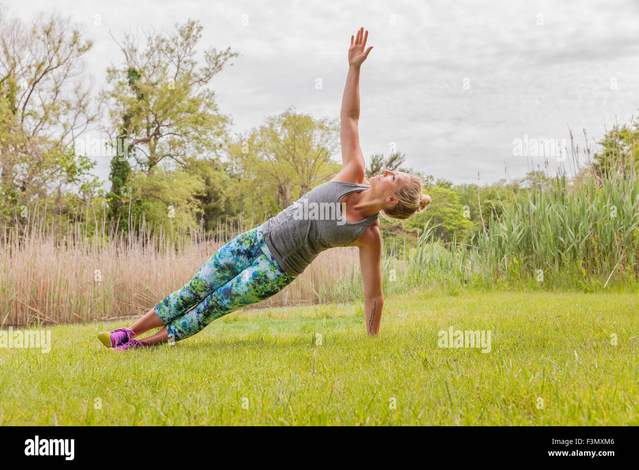 Woman in side plank pose - Stock Image
