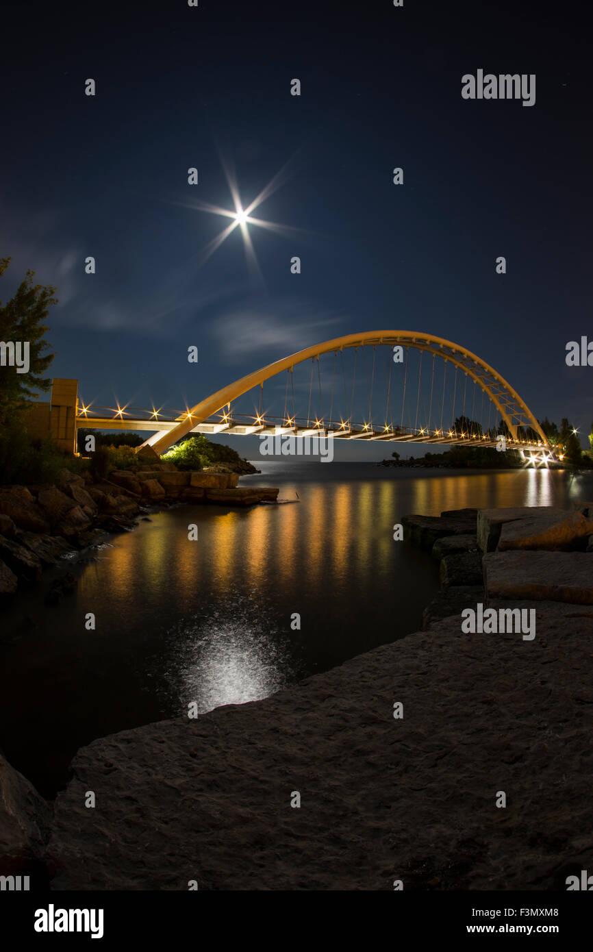 Illuminated arch bridge at night with a harvest moon. Stock Photo