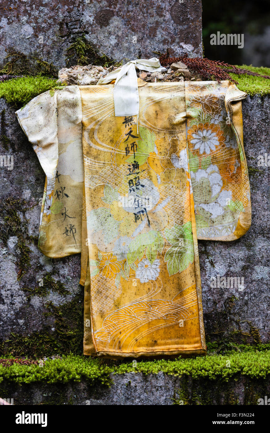 Japan, Koyasan, Okunion cemetery, old faded small yellow jacket with ...