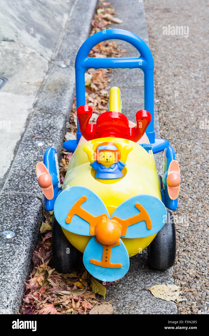 Japanese pusher car at side of road. Blue Propeller blades on front of yellow plastic car with blue pusher bar at - Stock Image
