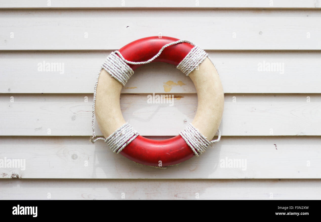 Decorative life preserver on rustic weather board wall, hanging on the side of a beach house - Stock Image