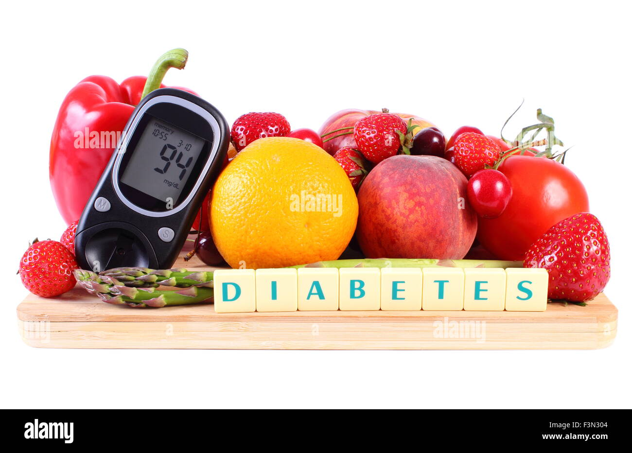 Glucometer with fresh ripe fruits and vegetables on wooden cutting board, concept of diabetes, healthy food, nutrition - Stock Image