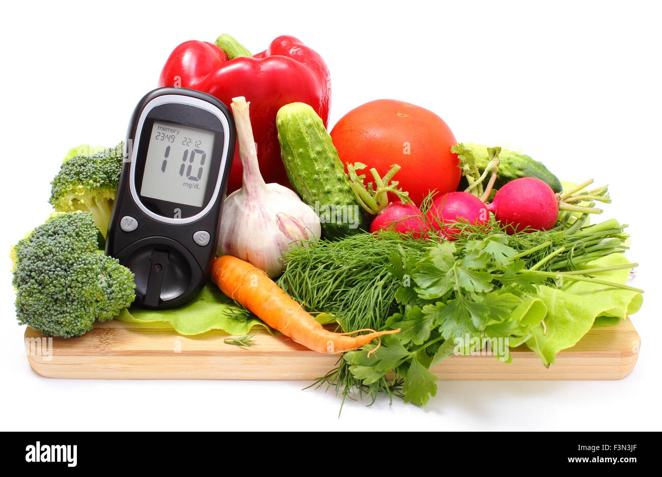 Glucometer and fresh ripe raw vegetables lying on wooden cutting board, desk of healthy organic vegetables, concept - Stock Image
