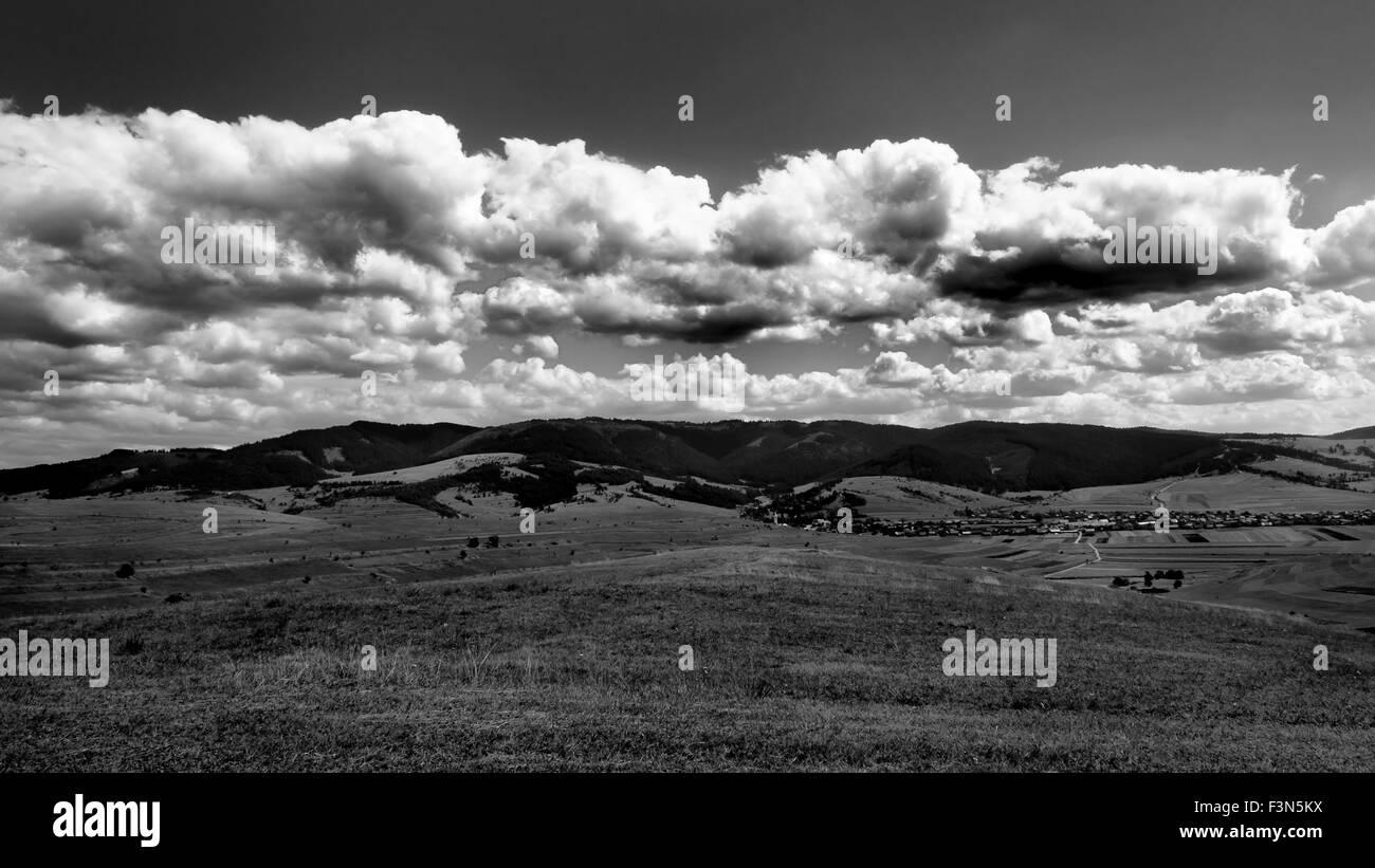 High contrast black and white autumn landscape with big clouds in Transylvania, Romania, Szeklerland, Alcsik. - Stock Image