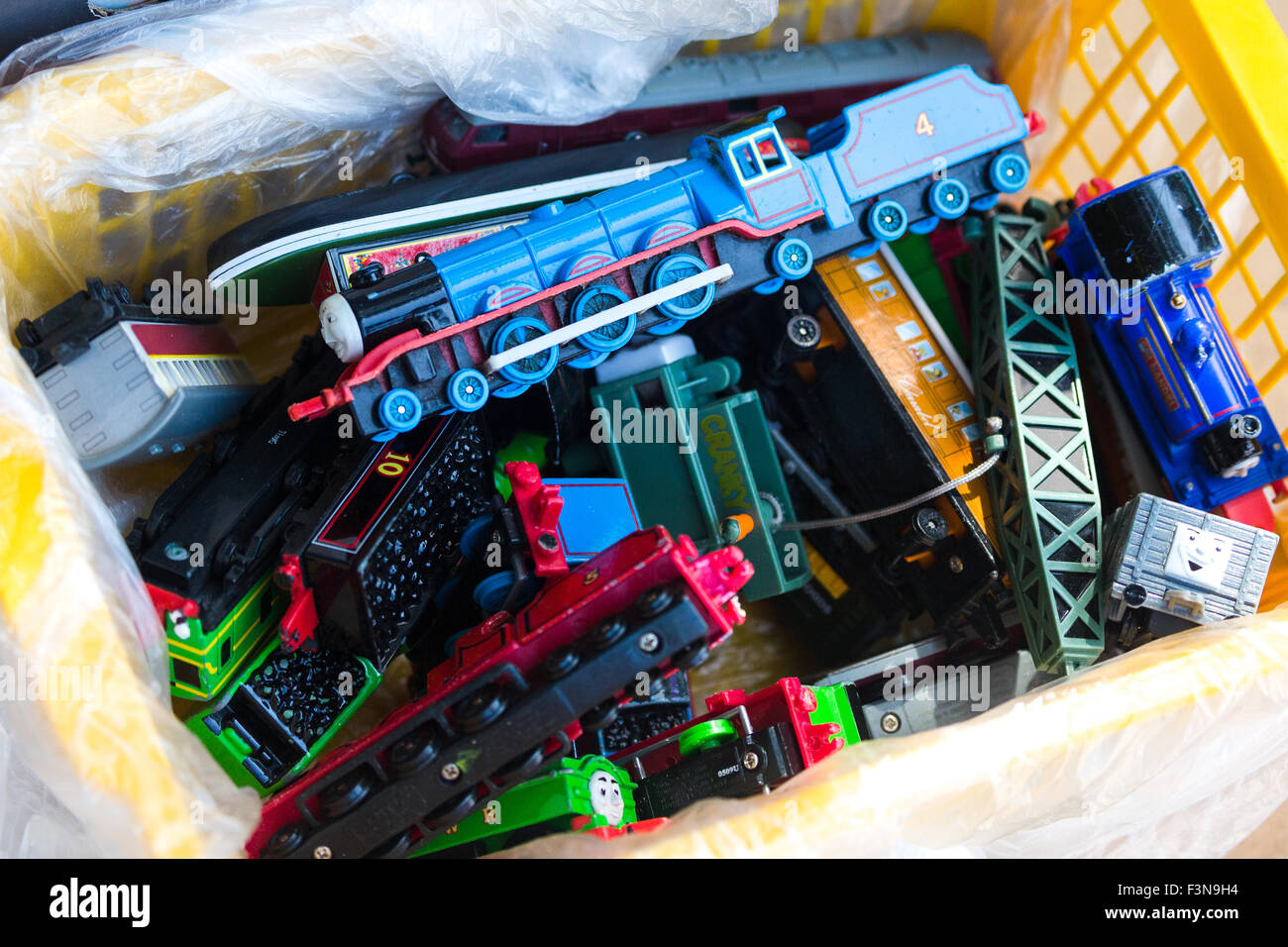 Box of old toy trains for sale. Yard sale Norfolk England UK - Stock Image