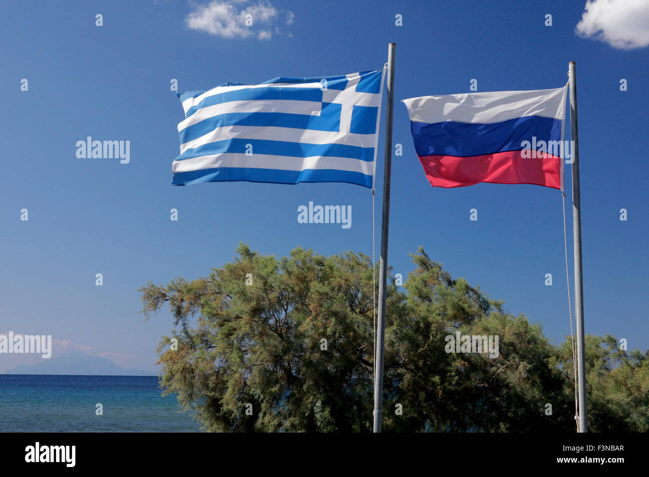 Russian & Greek flags of the Russian naval memorial and Holy mt. Athos (Chalkidiki peninsula) silhouetted on - Stock Image