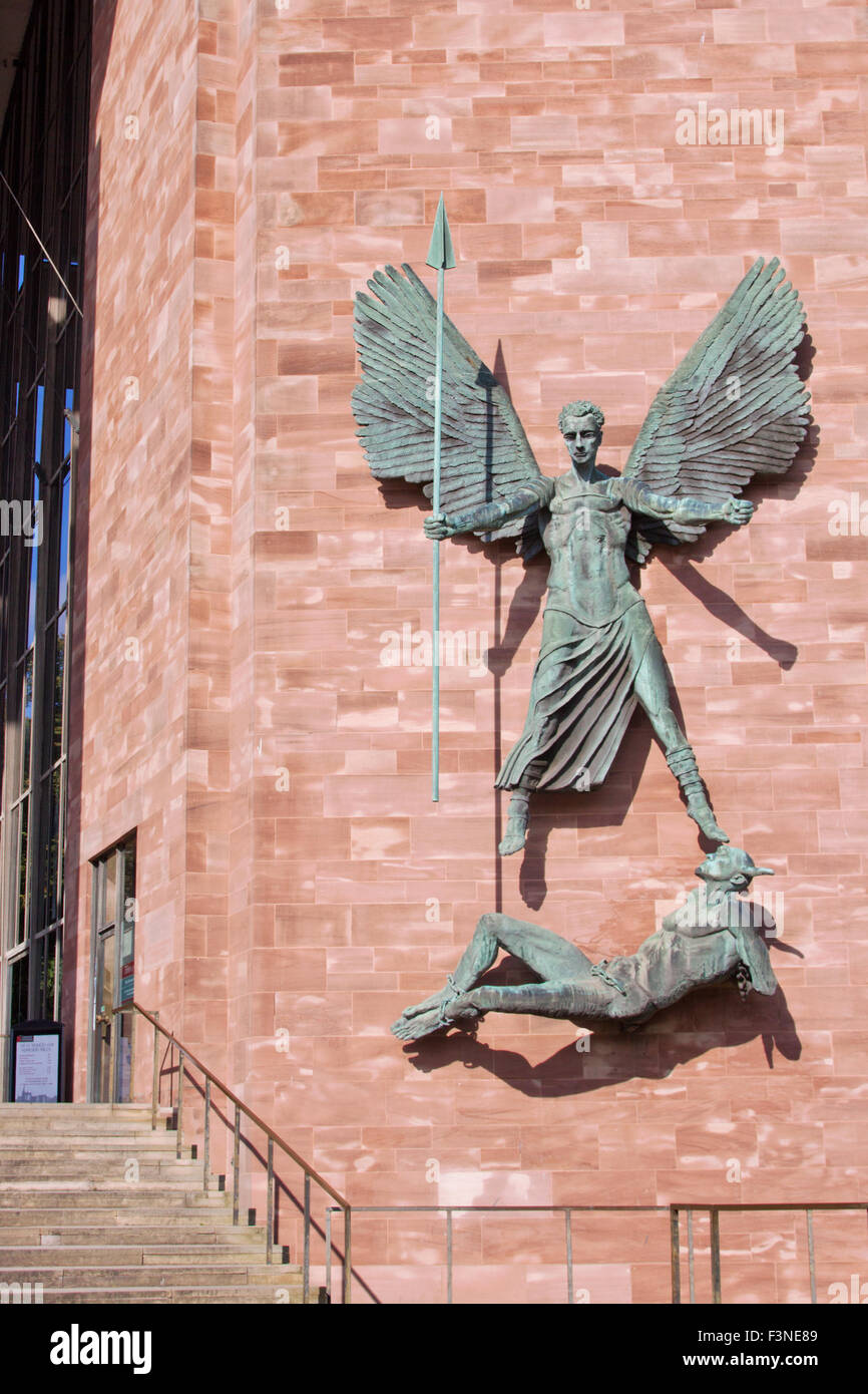 Bronze statue of St Michael conquering the Devil by Jacob Epstein, mounted on a wall next to the entrance to Coventry - Stock Image