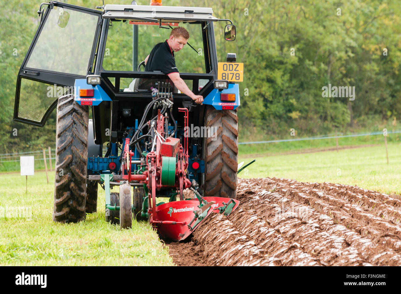 Lisburn, Northern Ireland. 10 Oct 2015 - A competitor uses a tractor to plough a field at the Northern Ireland Ploughing - Stock Image