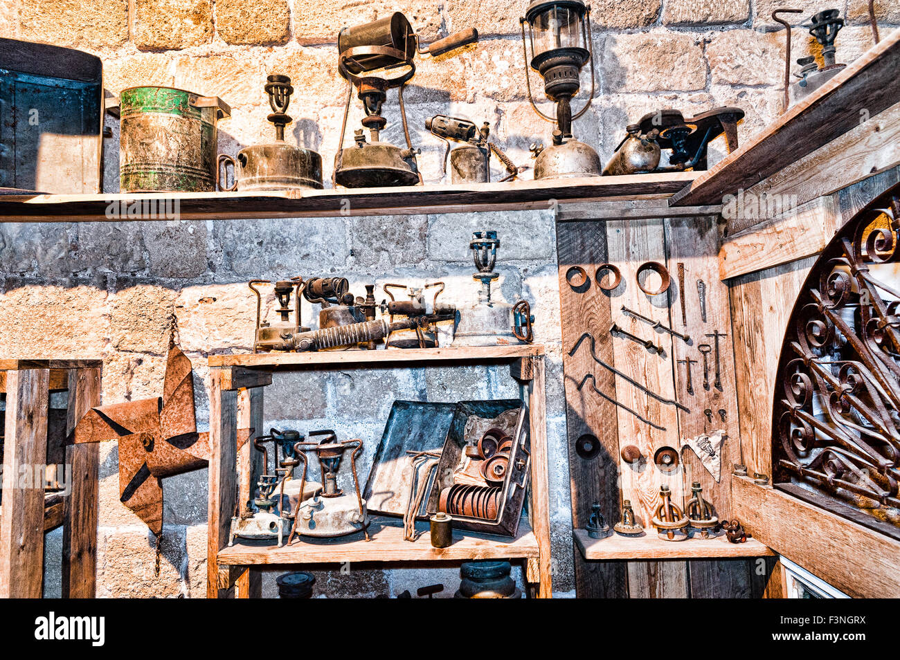 Junk shop filled with things that are gathering dust on the shelves. Bronza and copper utensils, stoves and kerosene - Stock Image