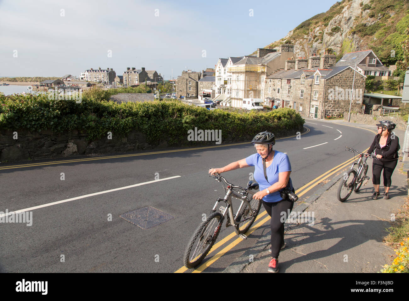 Cyclists walking up the steep hill out of Barmouth on there way to the cycleway over Barmouth railway bridge cycleway. - Stock Image