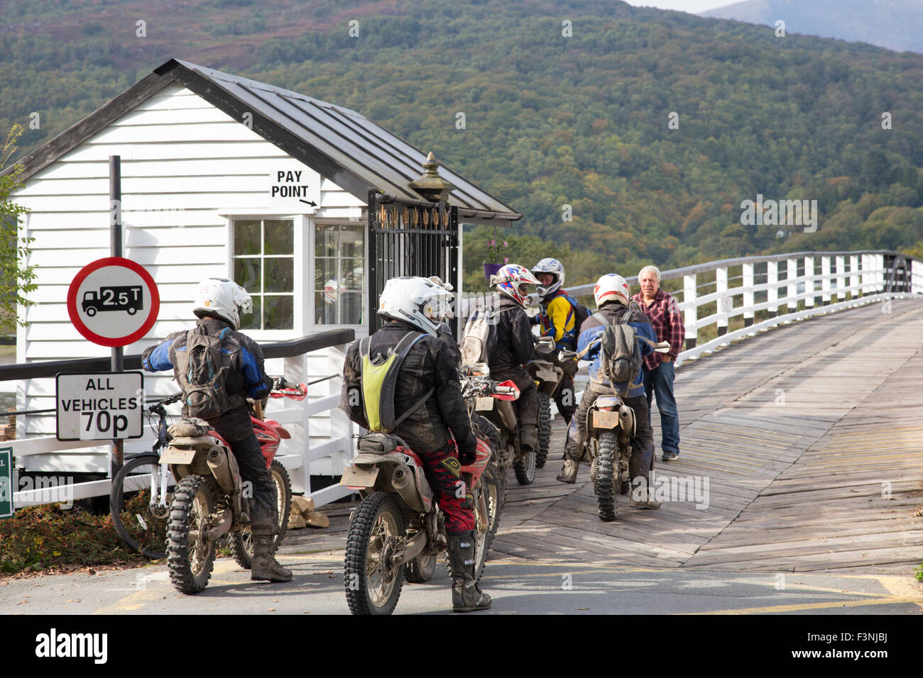 Trail bikers on Penmaenpool wooden toll bridge crossing the River Mawddach, Snowdonia National Park, Gwynedd, North - Stock Image