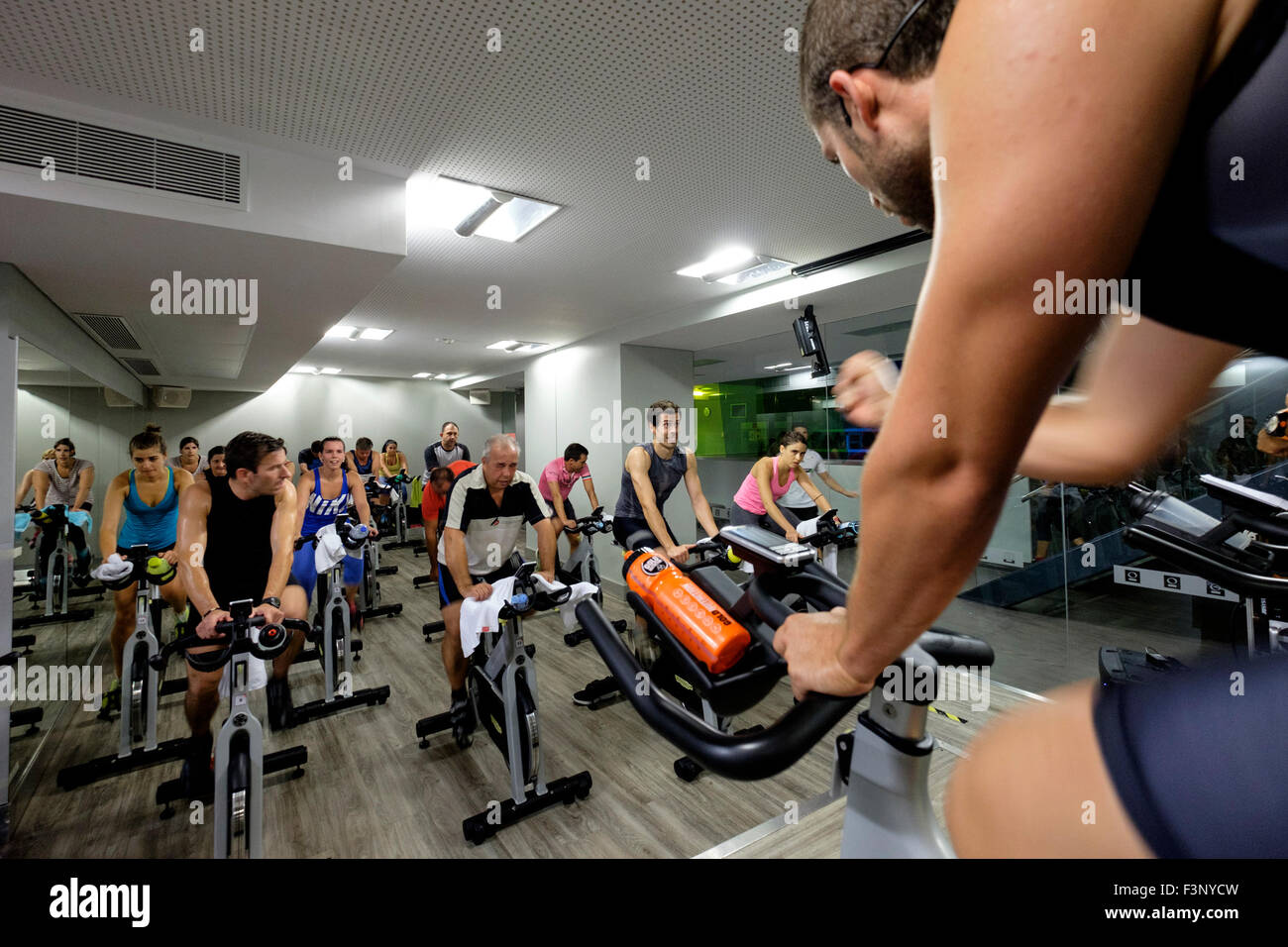 Fitness instructor encourages people riding stationary bicycles during a spinning class at the gym - Stock Image