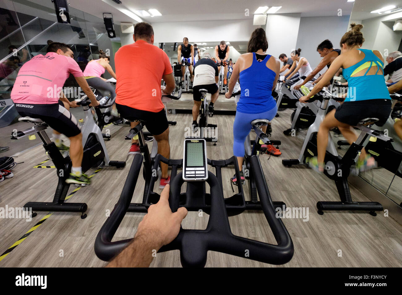First person perspective of a man riding a stationary bicycle during a spinning class at the gym - Stock Image