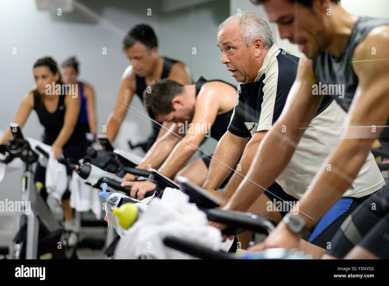 Side view of people riding stationary bicycles during a spinning class at the gym - Stock Image
