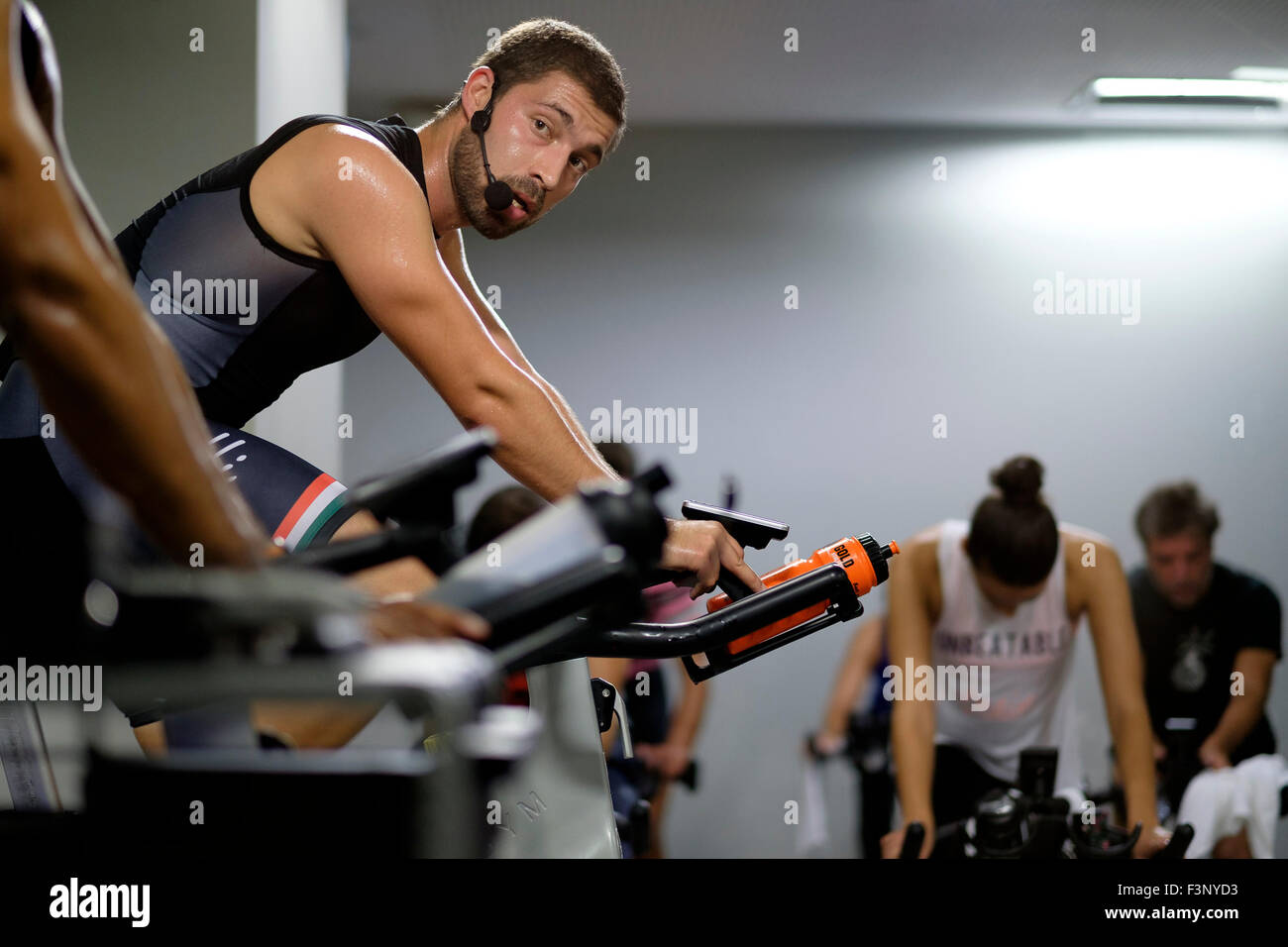 Fitness instructor in front of people riding stationary bicycles during a spinning class at the gym - Stock Image