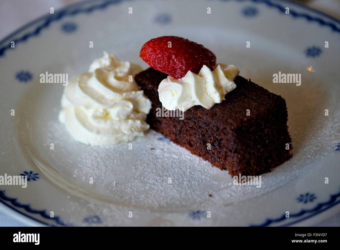 Chocolate cake dessert with whipped cream and a strawberry - Stock Image
