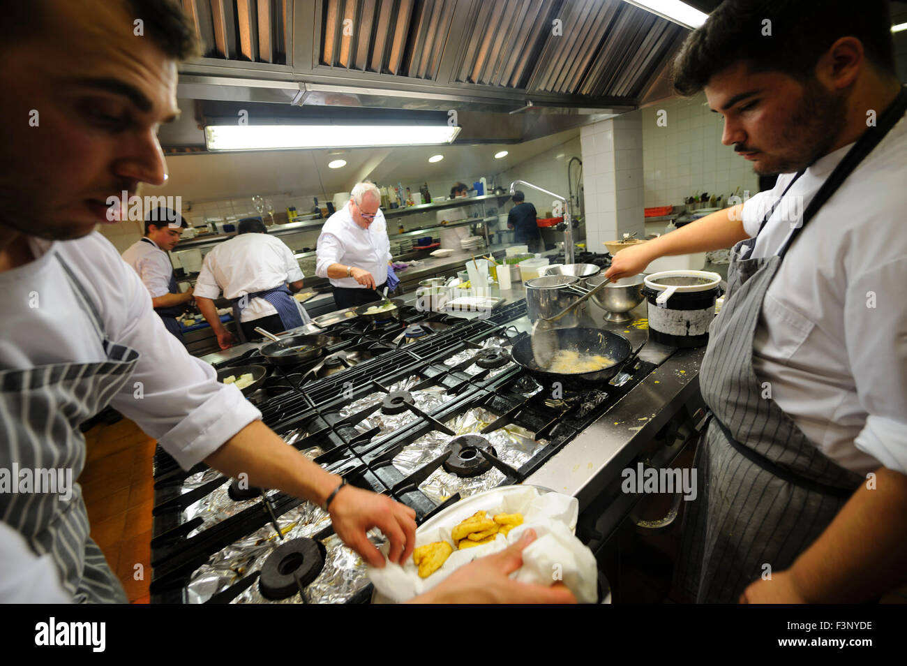 busy restaurant kitchen. Cooks Frying Fish On A Professional Restaurant Kitchen - Stock Image Busy