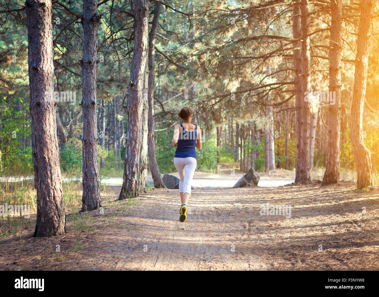 Young woman running on a rural road at sunset in autumn forest. Lifestyle sports background Stock Photo