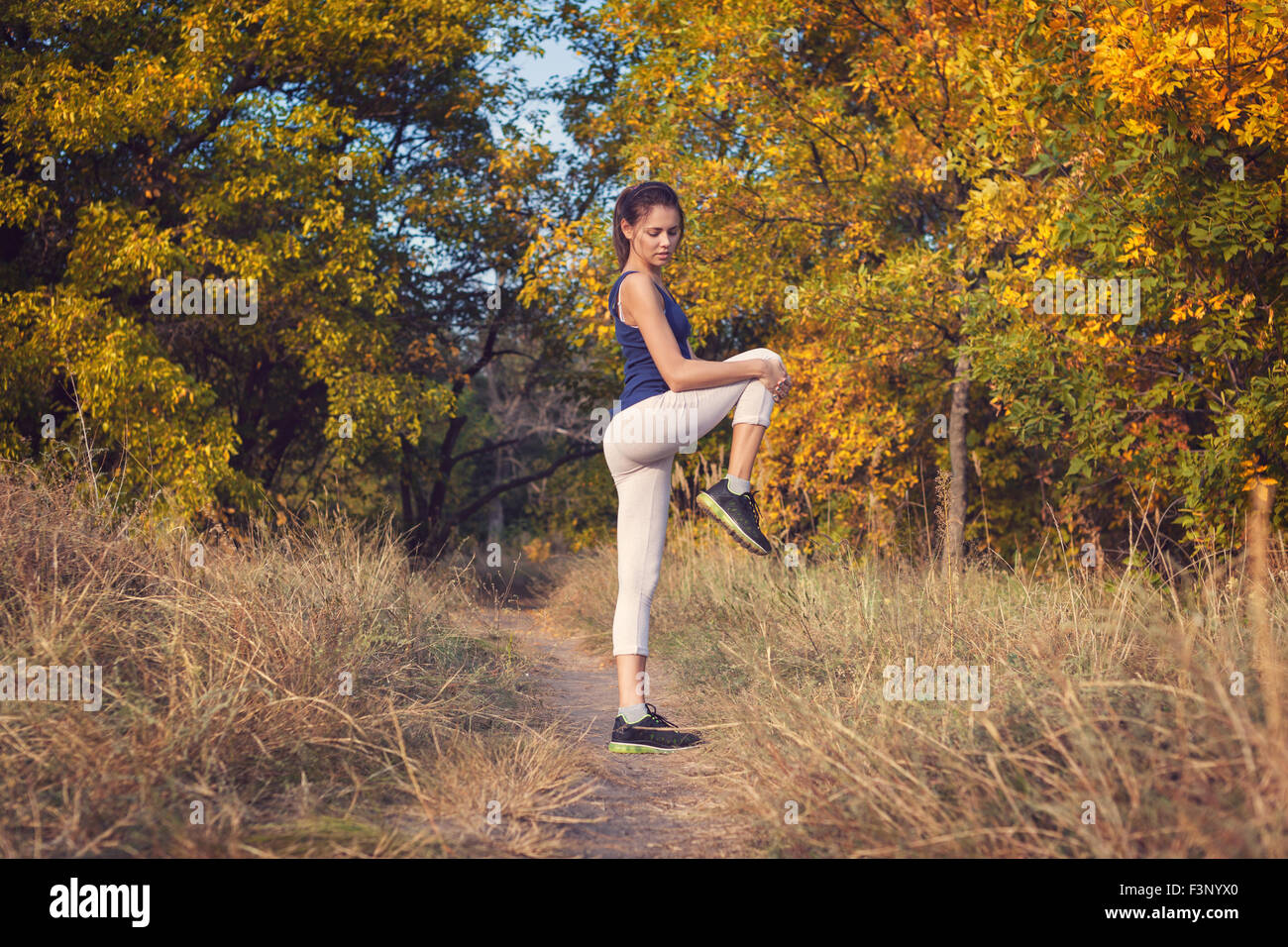 Young beautiful girl sports in the autumn forest at sunset - Stock Image