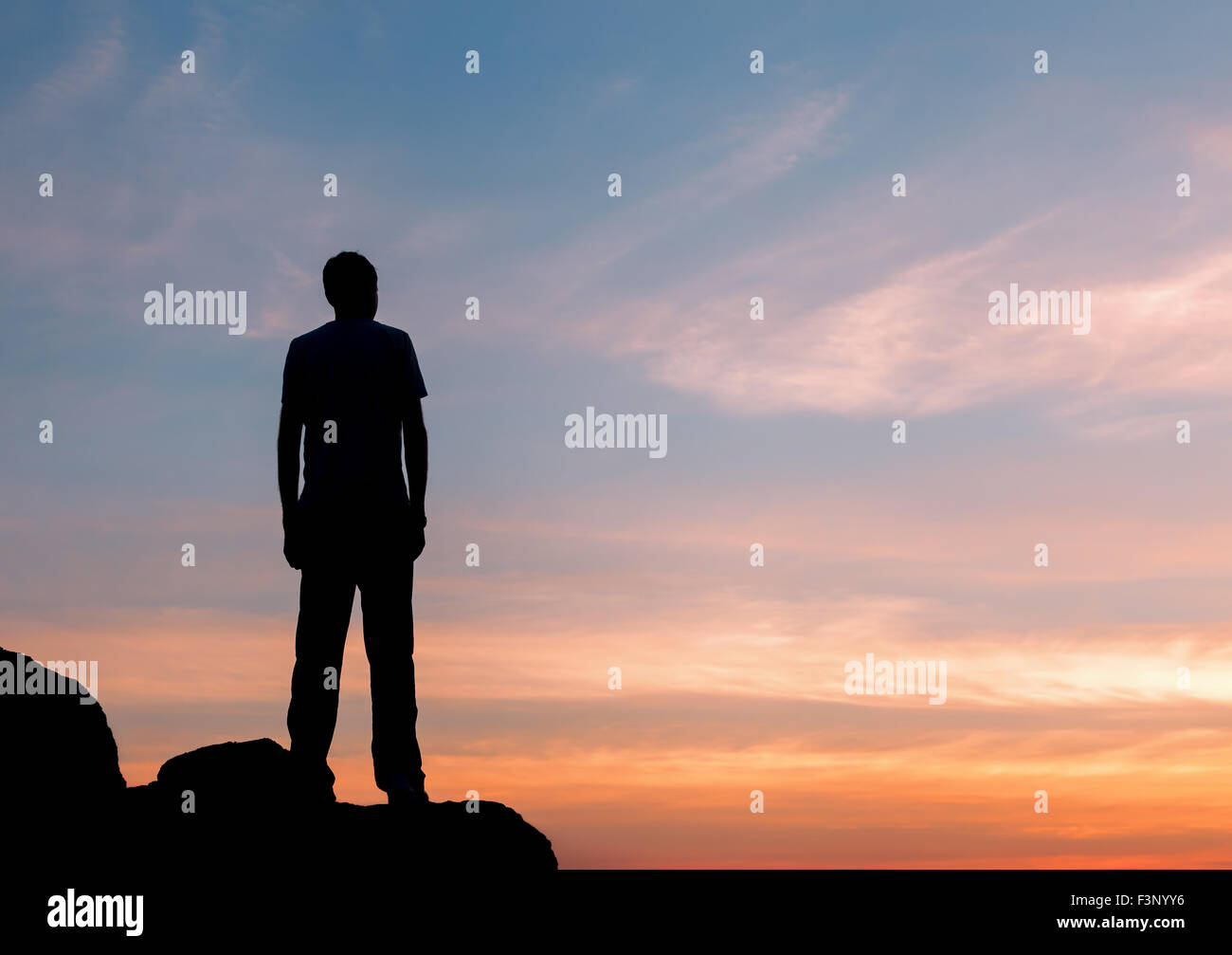 Silhouette of a man with raised-up arms at the beautiful sunset on the mountain. Background - Stock Image