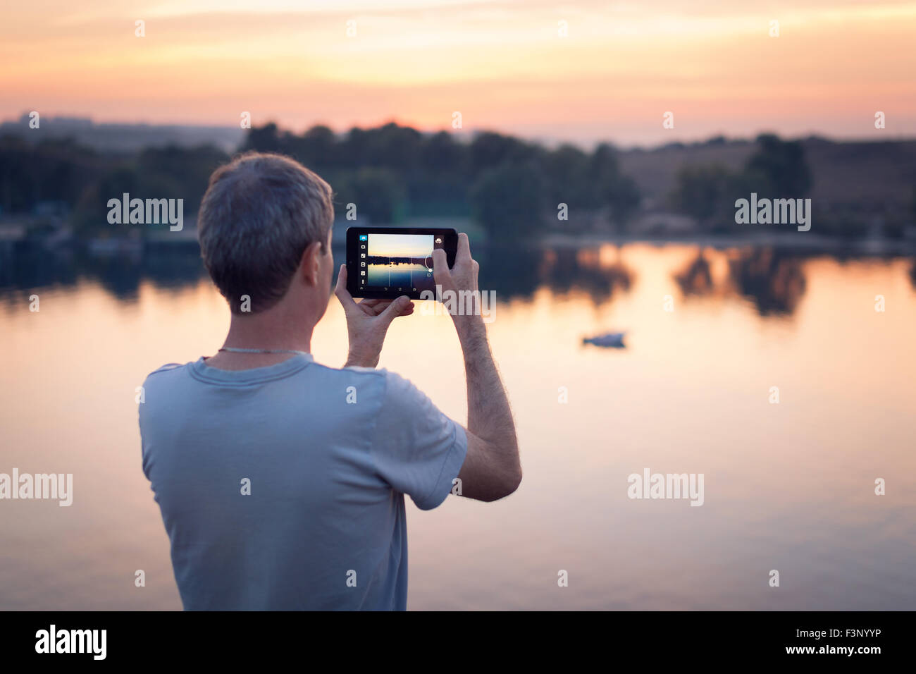 Man with tab makes photo of the sunset. Background - Stock Image