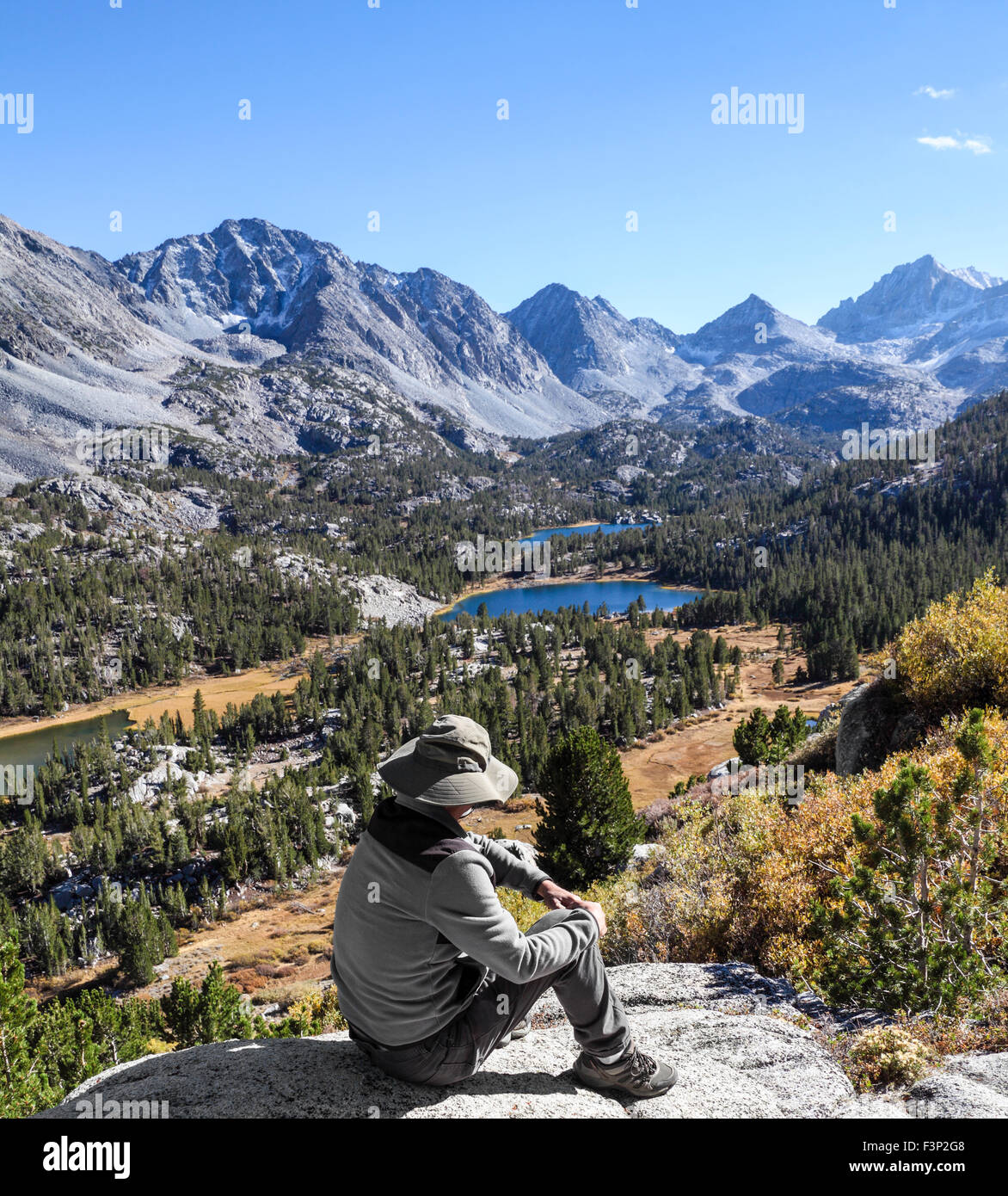 Resting hiker gazes at Little Lakes Valley in Rock Creek Canyon in the Eastern Sierra in Northern California Stock Photo