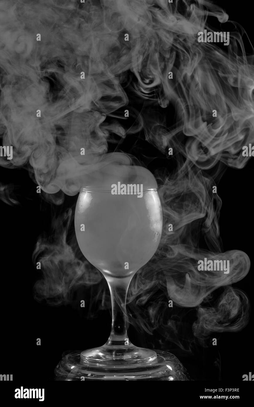 Abstract art  Hookah smoke into cocktail glass on a black