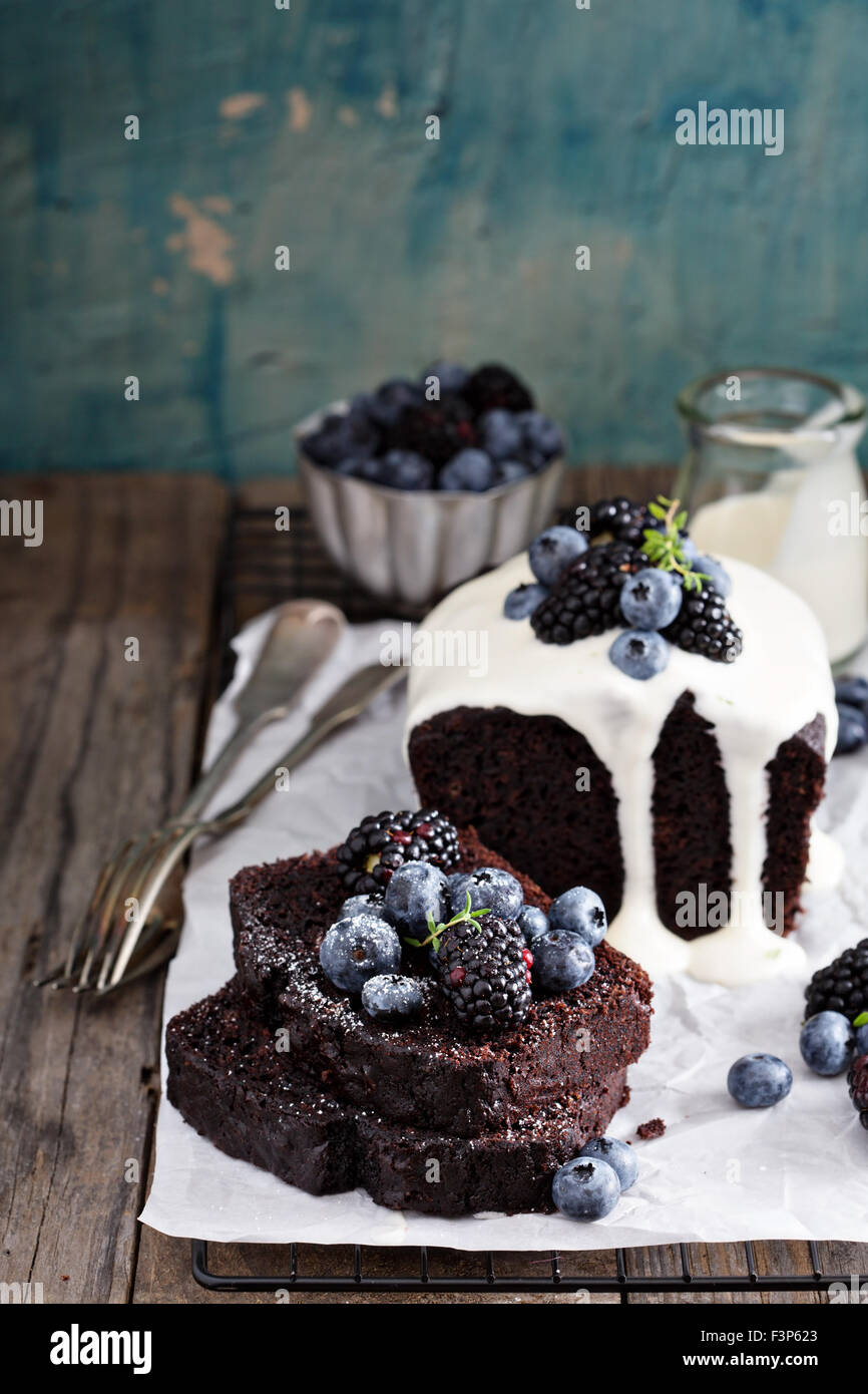 Chocolate loaf cake sliced decorated with frosting and berries - Stock Image