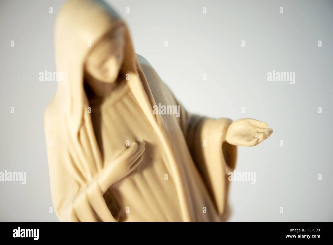 Figure of the Virgin Mary with her head bowed in humility depicting charity as she holds out her extended palm, - Stock Image