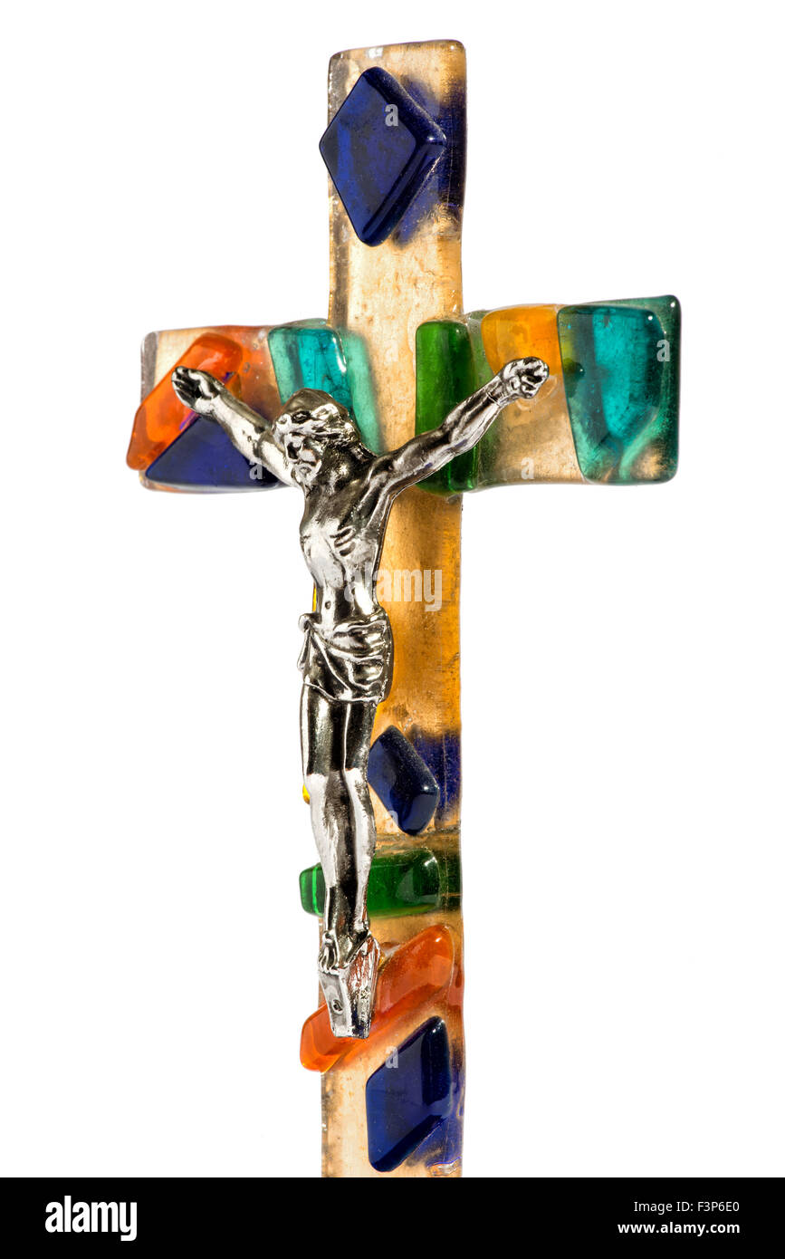 Close up angled view of the figure of a crucified Christ on a colorful decorative glass cross isolated on a white - Stock Image