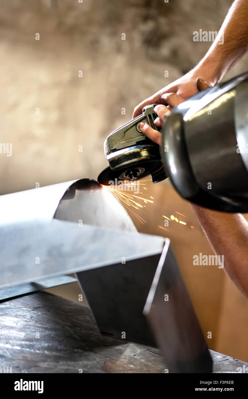 Metal worker using a angle grinder - Stock Image