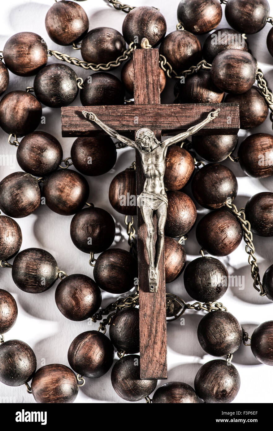 Wooden rosary with a crucifix depicting a crucified Christ on a wooden cross - Stock Image